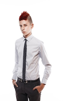 Portrait of serious teen with red mohawk wearing shirt and tie while looking at camera isolated