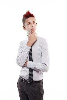 Portrait of serious teen with red mohawk wearing shirt and tie while looking thoughtful isolated
