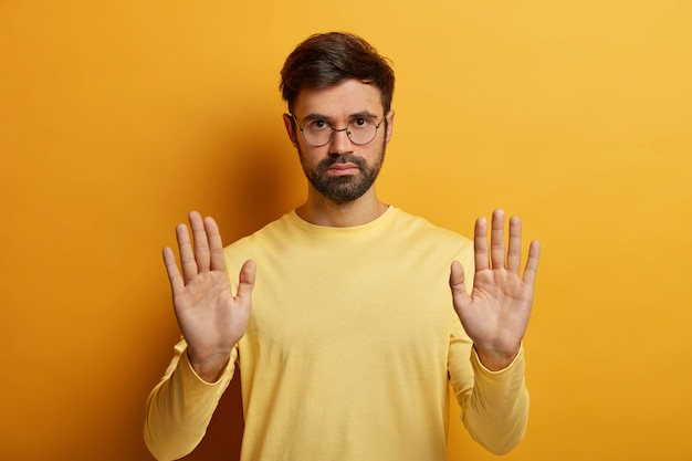 Portrait of serious unshaven man makes stop symbol, demonstrates restriction, refusal or rejection, asks not bother him wears round spectacles and jumper isolated on yellow wall has warning expression