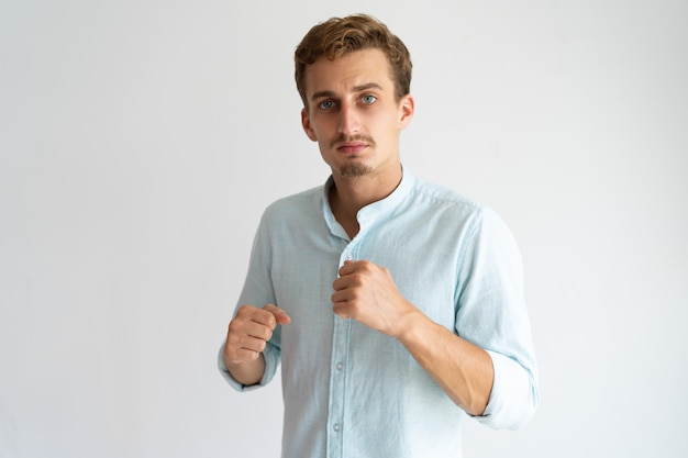 Portrait of serious upset guy ready for fight.