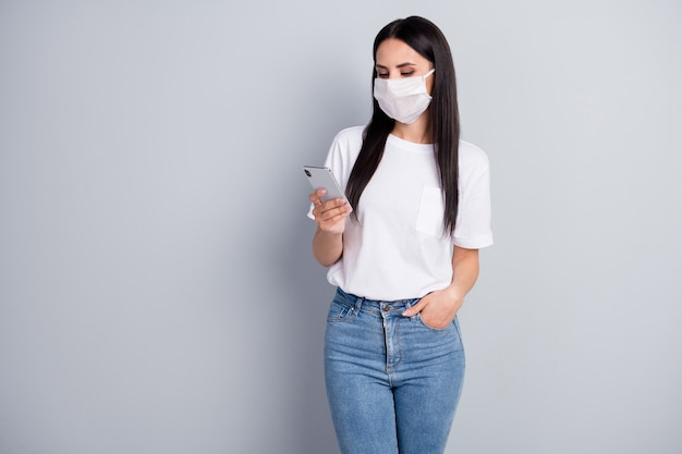 Portrait of serious worried girl use smartphone search epidemic covid19 information follow share repost news wear tshirt denim jeans medical mask isolated over gray color background