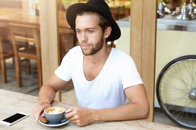 Ritratto di giovane uomo barbuto serio in cappello alla moda con cappuccino con cookie mentre vi rilassate al bar da solo
