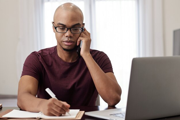 Portrait of serious young businessman calling on phone and taking notes in planner when talking on phone with client