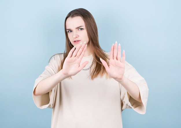Portrait of serious young european woman standing with arms outstretched showing stop gesture isolated on blue wall