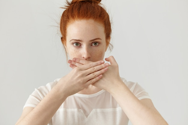 Portrait of serious young ginger european woman covering mouth with both hands keeping a secret. freckled redhead female in blouse doesn't want to spread rumors or some confidential information