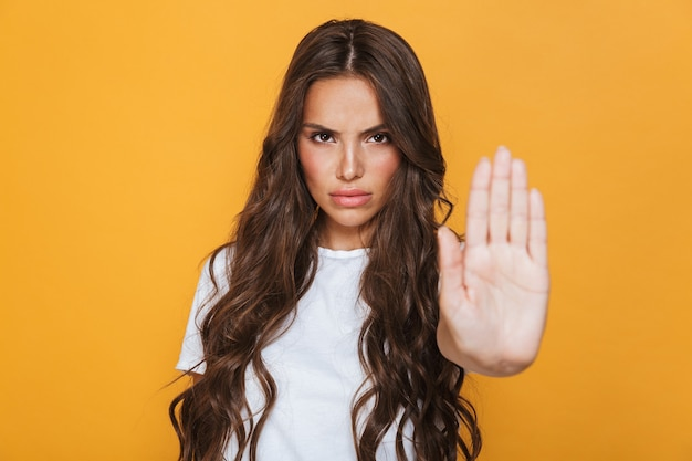 Portrait of a serious young girl with long brunette hair standing over yellow wall, showing stop gesture