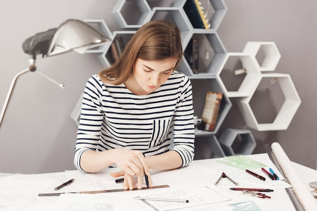 Portrait of serious young good-looking female architect sitting at her workplace, making drawings with pencil and ruler, trying not to make a mistake in blueprints.