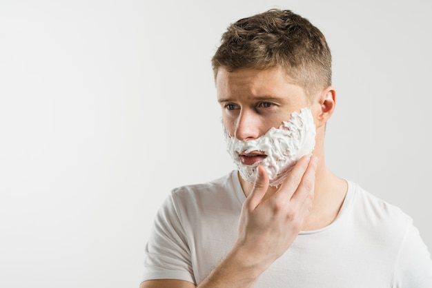 Portrait of a serious young man applying shaving foam on his cheek