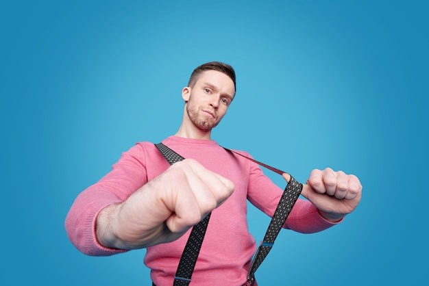 Portrait of serious young man in pink sweater pulling trousers suspenders