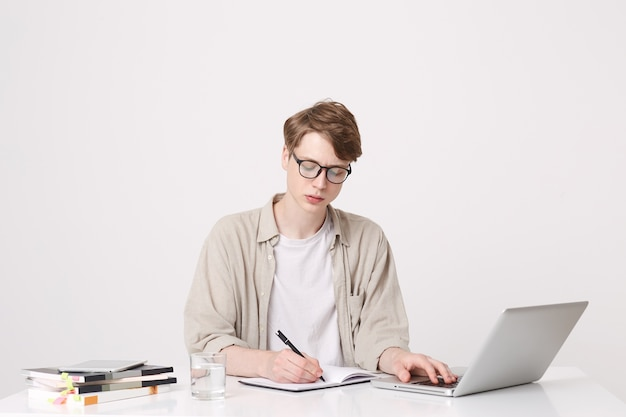 Portrait of serious young man student wears beige shirt and spectacles writing and study at the table using laptop computer and notebooks isolated over white wall