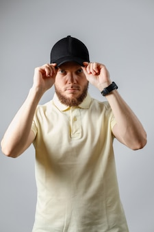 Portrait of serious young man in a yellow t-shirt and black cap on gray.