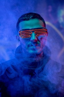 Portrait of serious young mixed race man in neon geometric goggles standing in smoked dark blue room