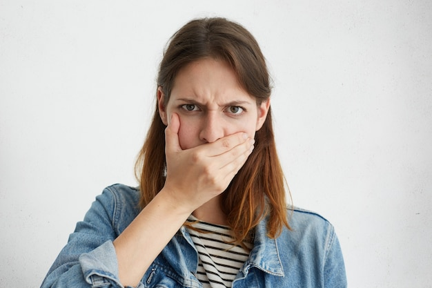 Portrait of serious young woman in denim jacket covering mouth with hand while concealing secret