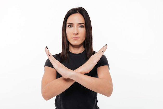 Portrait of a serious young woman showing crossed hands gesture