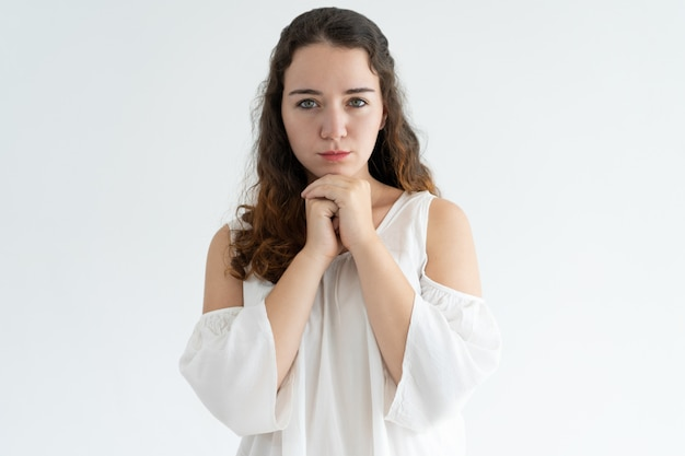 Portrait of serious young woman standing with her hands clasped