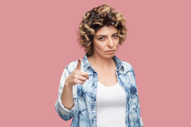 Portrait of serious young woman with curly hairstyle in casual blue shirt standing, looking at camera with warning hand. indoor studio shot, isolated on pink background.