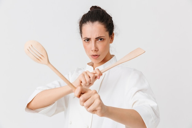 Portrait of a serious young woman with kitchen utensils