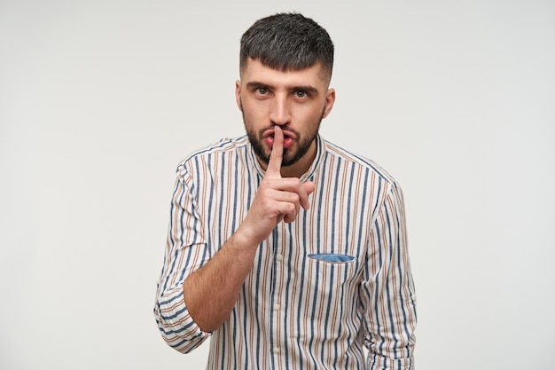 Portrait of severe young short haired bearded male frowning his eyebrows and keeping index finger on his lips while asking to be quiet, isolated over white wall