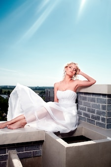 Portrait of sexy beautiful fashion blond female girl model bride posing in white flying dress in the roof with makeup and hairstyle.blue sky. sun