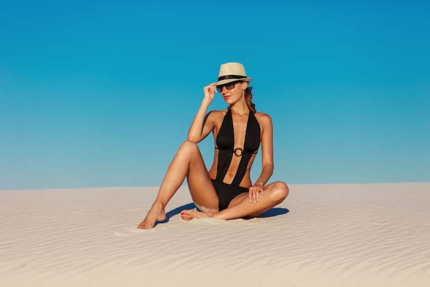 Portrait of sexy beautiful tanned model woman posing in fashion black bikini, hat and sunglasses on sand beach