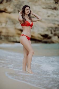 Portrait of sexy beautiful tanned woman posing in colorful swimwear bikini at the sea coast.