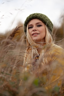 Portrait of sexy beautiful woman in knitted green hat and yellow coat, smokey eyes make-up , flying hairs in dry grass