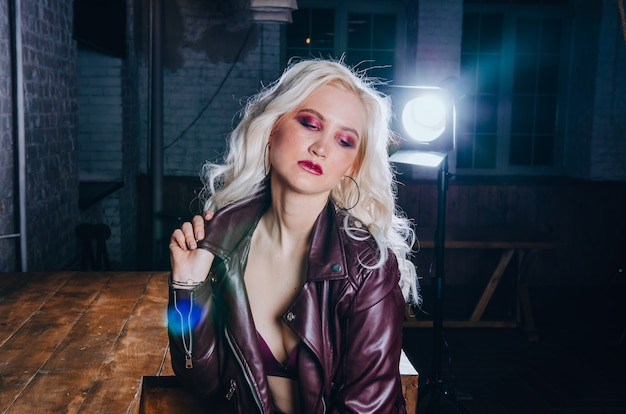 Portrait of sexy blonde girl in purple leather jacket