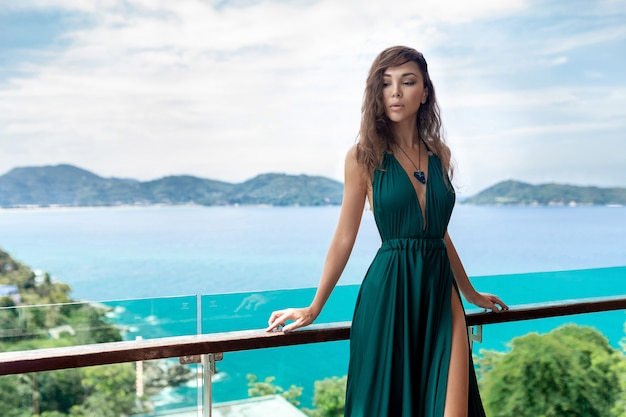Portrait of a sexy brunette in evening dress with a massive embellishment on her chest standing on the terrace looking down