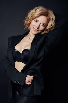 Portrait of sexy business women blonde in a black jacket, bare body, perfect figure girls, erotic sensual look, daring image, the woman in black