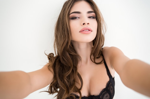 Portrait of a sexy charming woman in lingerie making selfie photo isolated on a white background