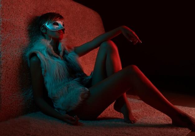 Portrait of sexy girl in fur jacket wearing mask