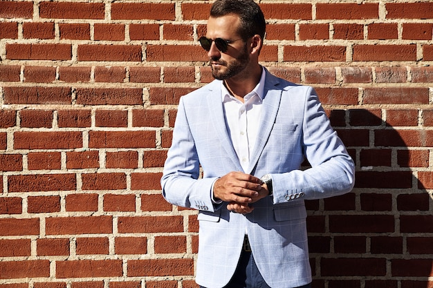 Portrait of sexy handsome fashion businessman model dressed in elegant blue suit posing near brick wall on the street background. metrosexual