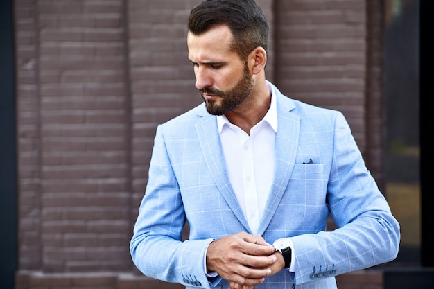 Portrait of sexy handsome fashion businessman model dressed in elegant blue suit posing on street background. metrosexual