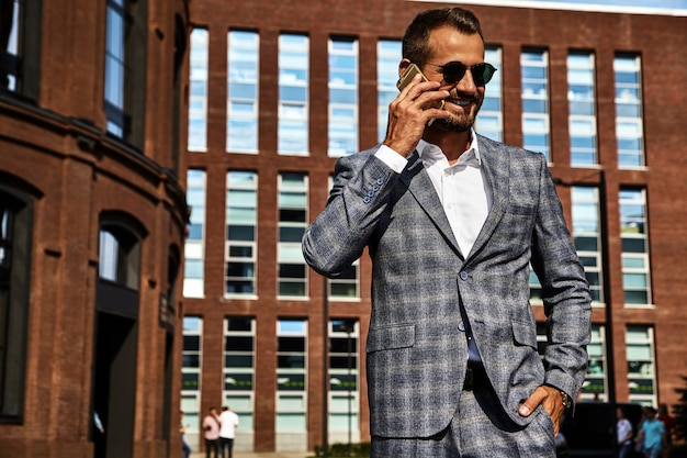 Portrait of sexy handsome fashion businessman model dressed in elegant checkered suit having business mobile conversation on smartphone on street. metrosexual