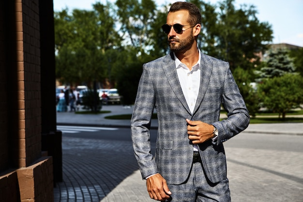 Portrait of sexy handsome fashion businessman model dressed in elegant checkered suit posing on street background. metrosexual