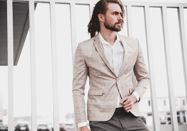 Portrait of sexy handsome fashion male model man dressed in elegant beige checkered suit