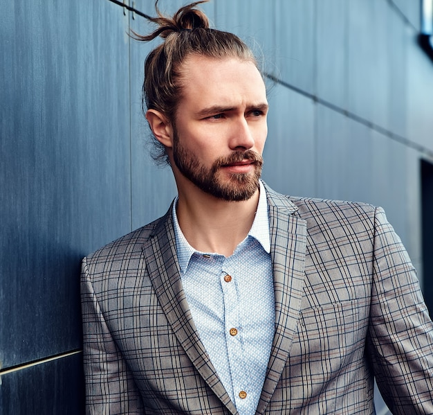 Portrait of sexy handsome fashion male model man dressed in elegant checkered suit posing near dark blue wall in the street background;