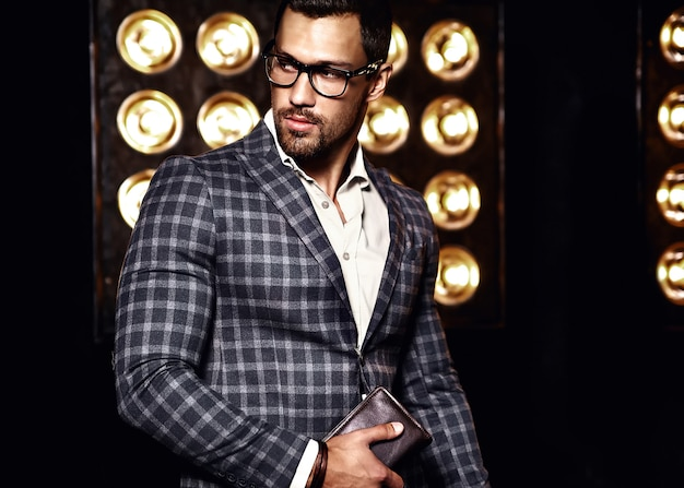 Portrait of sexy handsome fashion male model man dressed in elegant suit on black studio lights background in glasses