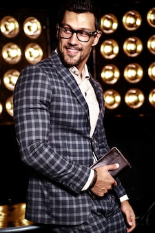 Portrait of sexy handsome fashion male model man dressed in elegant suit on black studio lights background in glasses