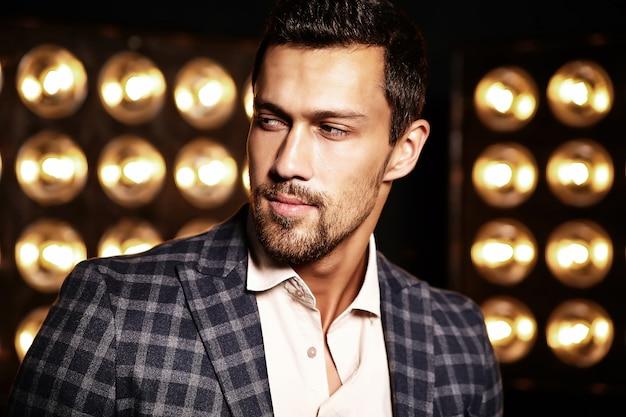 Portrait of sexy handsome fashion male model man dressed in elegant suit on black studio lights background