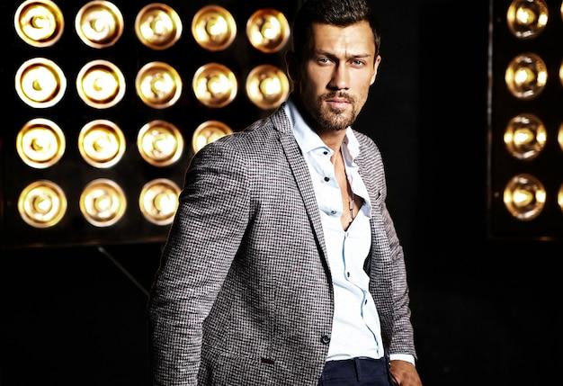 Portrait of sexy handsome fashion male model man dressed in elegant suit on studio lights background