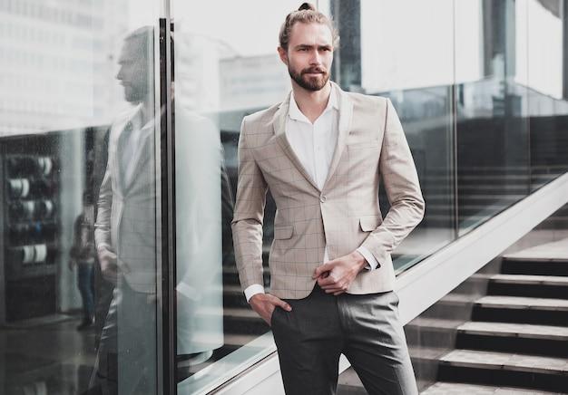Portrait of sexy handsome man dressed in elegant beige checkered suit