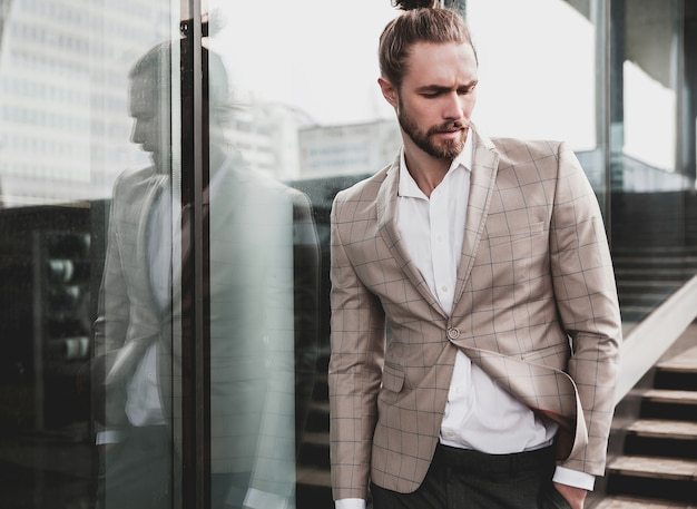 Portrait of sexy handsome man dressed in elegant beige checkered suit