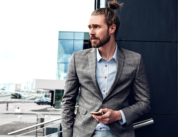 Portrait of sexy handsome man dressed in elegant gray checkered suit