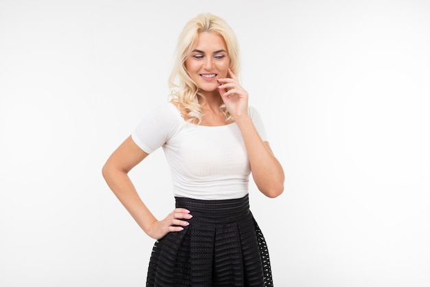 Portrait of a sexy lady in a white top and black skirt posing holding her hand at the chin on a white studio background with copy space