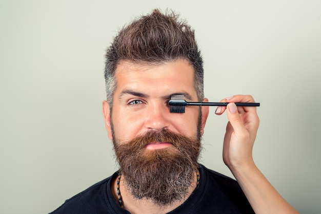 Portrait of sexy male with beard model face and tweezers near brows. beauty concept. eyebrow correction. closeup of beautiful funny man plucking eyebrows. high resolution