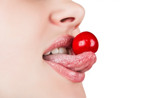 Portrait of sexy mouth eating cherry isolated on the white background
