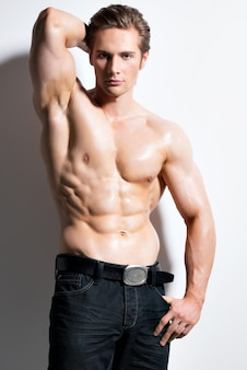 Ritratto di un uomo bello muscoloso sexy con le mani dietro la testa in posa su un muro bianco.