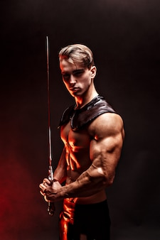 Portrait of sexy muscular man holding sword