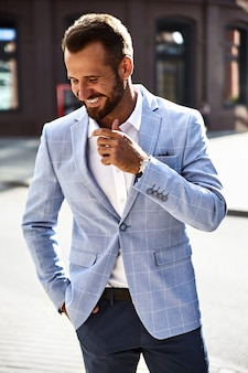 Portrait of sexy smiling handsome fashion businessman model dressed in elegant blue suit posing on street background. metrosexual